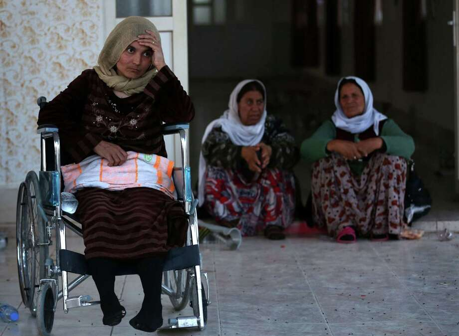 Yazidi women look on upon arrival at a medical center in the northern Iraqi town of Altun Kupri, after the Islamic State freed more than 200 Yazidis the group had held captive for months. Photo: SAFIN HAMED / AFP / Getty Images / AFP