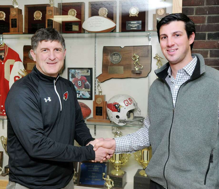 At left, Gus Lindine, Greenwich High School athletic director, shakes hands with John Marinelli who was named the new Greenwich High School football coach during an announcement at the school in Greenwich, Conn., Wednesday, April 8, 2015. Marinelli is the son of New Canaan High School football coach, Lou Marinelli. John Marinelli served as an assistant football coach at New Canaan High School under his father. Photo: Bob Luckey / Greenwich Time