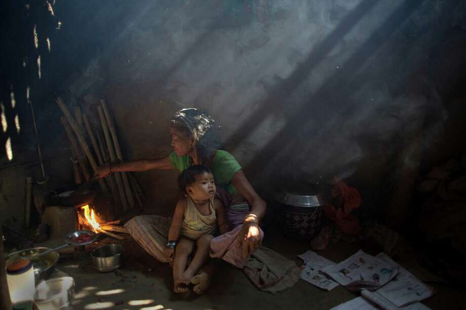 An elderly Indian woman cooks using firewood at her home at Gobhali village on the outskirts of Gauhati, India. Every evening, hundreds of millions of Indian women hover over crude stoves making dinner for their families. Photo: Anupam Nath / Associated Press / AP