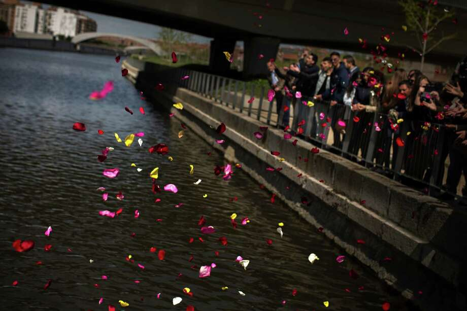 Roma residents throw flowers into Madrid's Manzanares River to pay homage to those killed during the Holocaust and other extermination campaigns. Photo: Andres Kudacki / Associated Press / AP