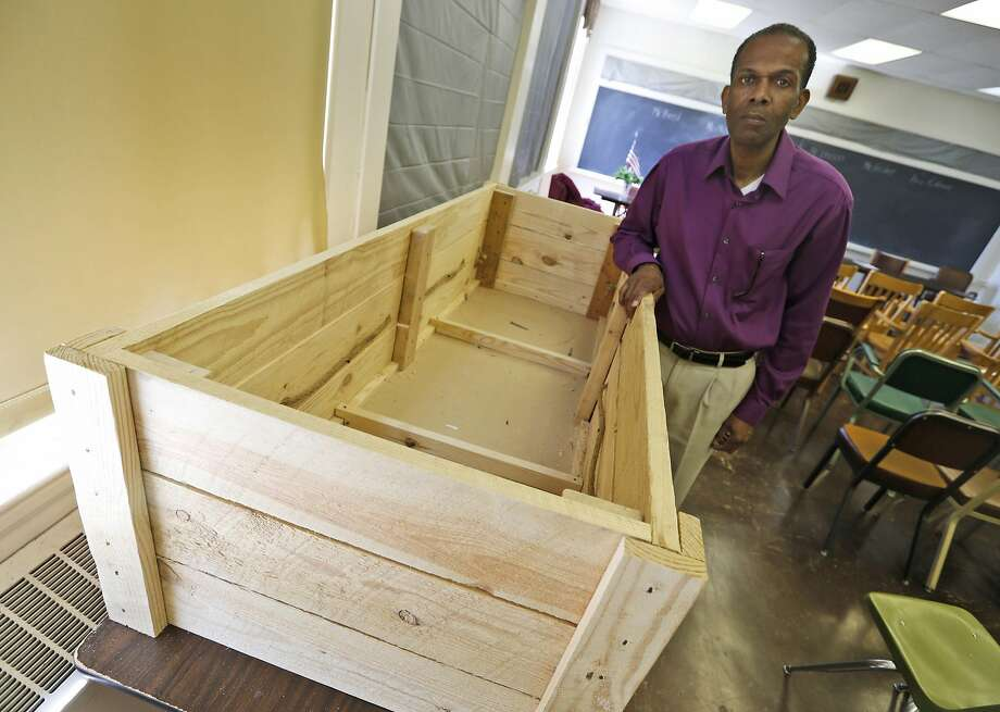 Rev. Alfred L. Jones III poses with a period style pine box coffin that will be used to represent former slave Hannah Reynolds, who was the lone civilian death at Appomattox at the end of the war, at the Carver-Price Legacy Museum in Appomattox, Va., Wednesday, April 1, 2015. Jones will deliver the eulogy for Reynolds whose death will be remembered during the 150th anniversary of the Civil War's end. (AP Photo/Steve Helber) Photo: Steve Helber, Associated Press