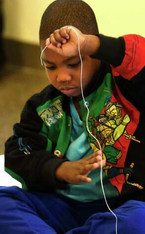 Robert Smith, 4, has some fun trying to navigate the kite string Wednesday, April 8, 2015, during kite making class at the Bach branch of the Albany Public Library in Albany, N.Y.  (Skip Dickstein/Times Union) Photo: SKIP DICKSTEIN / 00031251A