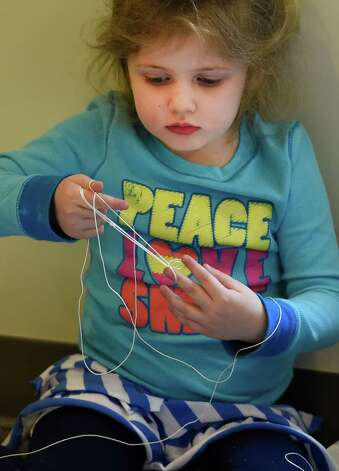 Sydney Sullivan, 3, has some fun trying to navigate the kite string Wednesday, April 8, 2015, during kite making class at the Bach branch of the Albany Public Library in Albany, N.Y.  (Skip Dickstein/Times Union) Photo: SKIP DICKSTEIN / 00031251A