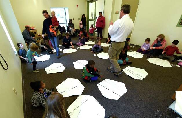 Children's librarian Lee Ricci gathers a large group of prospective kite flyers Wednesday, April 8, 2015, during kite making class at the Bach branch of the Albany Public Library in Albany, N.Y.  (Skip Dickstein/Times Union) Photo: SKIP DICKSTEIN / 00031251A