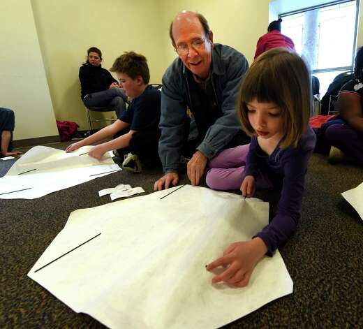 Alden Merrick assists Hannah Lavelle, 6, with her kite Wednesday, April 8, 2015, during kite making class at the Bach branch of the Albany Public Library in Albany, N.Y.  (Skip Dickstein/Times Union) Photo: SKIP DICKSTEIN / 00031251A
