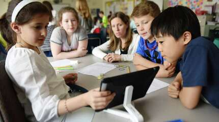 Teacher Crystal Kitselman, center, helps her fourth-graders, from left, Victoria Arlia, Rebecca Buehler, Owen Lanzarone and James Chang with a math problem on an iPad at North Mianus School in Greenwich, Conn. Wednesday, April 1, 2015.  With the advances of technology in the classroom, students and teachers are balancing digital learning on platforms like the iPad with traditional pen and paper, non-digital resources.