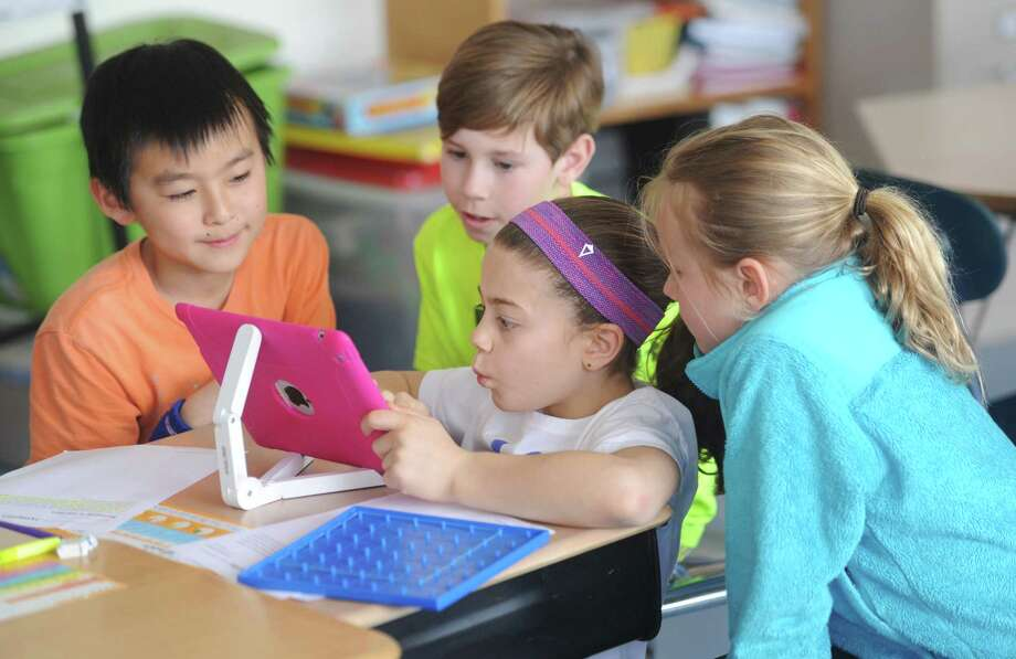 Fourth-graders, from left, Ibuki Matsushita, Will Duncan, Tori Ware and Logan Gilbrid use an iPad for a math project at North Mianus School in Greenwich, Conn. Wednesday, April 1, 2015.  With the advances of technology in the classroom, students and teachers are balancing digital learning on platforms like the iPad with traditional pen and paper, non-digital resources. Photo: Tyler Sizemore / Greenwich Time