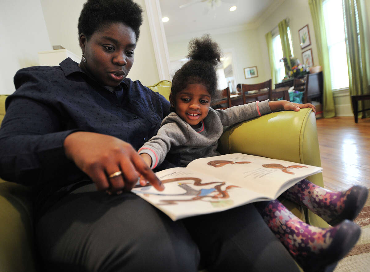 Veteran Carmen Roldan, originally from Stamford, and daughter Jayla Roldan, 3, read a book together at the Nicholas Maderas House at 66 Elmwood Avenue in Bridgeport, Conn. on Wednesday, April 8, 2015. The house, which provides transitional housing for female veterans, is part of the Homes for the Brave Network.