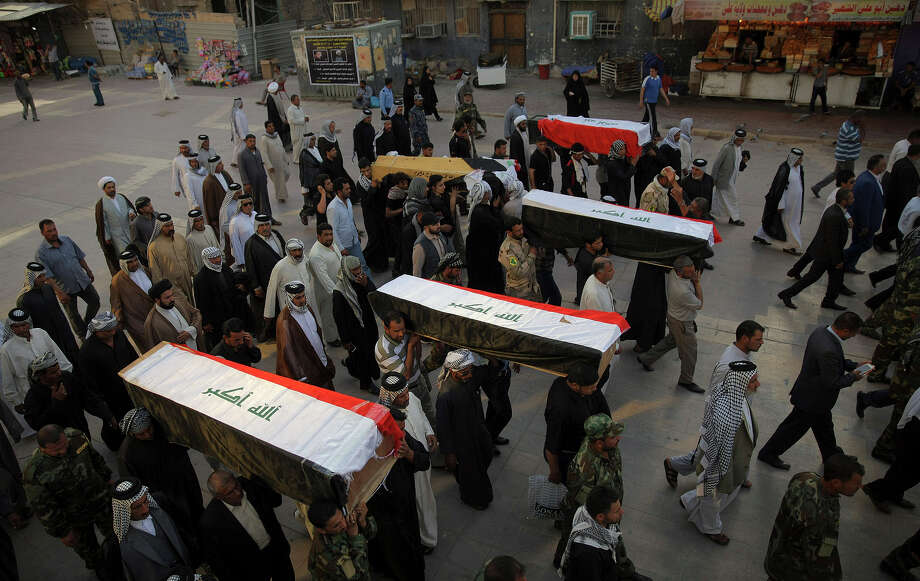 Mourners carry the flag-draped coffins of five Shiite militiamen killed on the outskirts of Tikrit during fighting with Islamic State militants, during their funeral procession in Najaf, 100 miles (160 kilometers) south of Baghdad, Iraq, Wednesday, April 8, 2015. (AP Photo/Jaber al-Helo) Photo: Jaber Al-Helo / Associated Press / ASSOCIATED PRESS