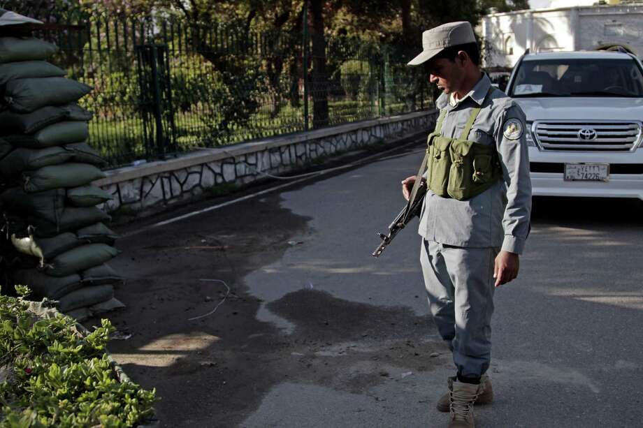An Afghan policeman looks at a bloodstained pavement at the site of an attack by an Afghan national army soldier who opened fire on U.S. troops, at the compound of the provincial governor, in Jalalabad, Afghanistan, Wednesday, April 8, 2015. An American soldier was killed in the shooting Wednesday in which at least two other U.S. troops were wounded. The incident happened after a meeting between Afghan provincial leaders and a U.S. Embassy official. (AP Photo/Rahmat Gul) Photo: Rahmat Gul, STF / AP