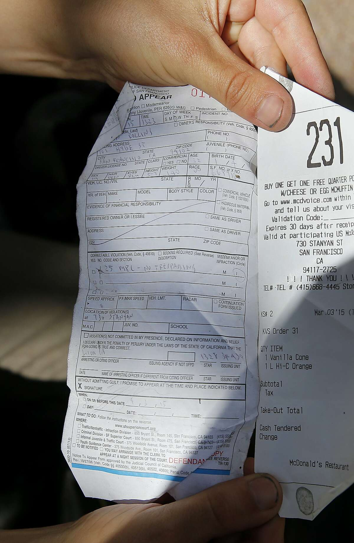 A young man shows off his ticket he received under the sit-lie law on Haight Street next to a receipt from the restaurant he visited. Sit-lie citations have declined sharply since they peaked in 2013, according to San Francisco Superior Court records.