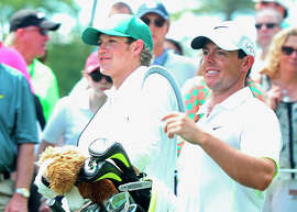 Rory McIlroy (right) walks with his caddie, Niall Horan of the band One Direction, during the Par 3 Contest at the Masters.