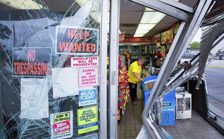 Carolina Estrada cleans up after a smash-and-grab at a Shell gas station along Hollister on Wednesday. Photo: Cody Duty, Staff / © 2015 Houston Chronicle
