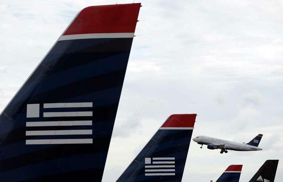 File: A bankruptcy judge approved the antitrust settlement between the Justice Department and AMR Corp. and US Airways Group Inc.  clearing the last step to a deal that will create the world's largest airline. ARLINGTON, VA - AUGUST 13:  A US Airways jet takes off at Ronald Reagan Washington National Airport August 13, 2013 in Arlington, Virginia. The U.S. Justice Department, and attorneys general from six states, filed legal actions today attempting to prevent the planned merger of US Airways and American Airlines as a violation of antitrust law.  (Photo by Win McNamee/Getty Images) Photo: Win McNamee, Staff / 2013 Getty Images