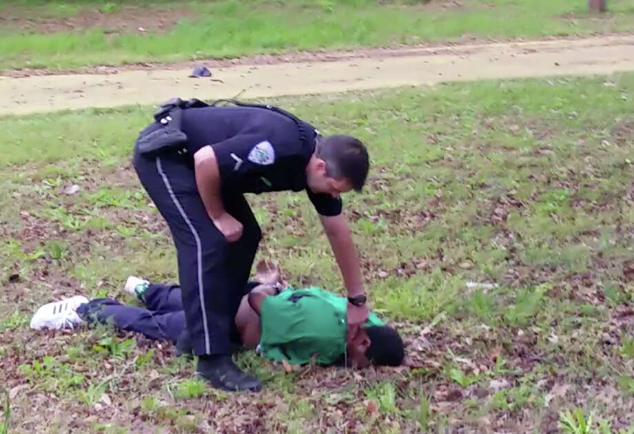 In this April 4, 2015, frame from video provided by attorney L. Chris Stewart representing the family of Walter Lamer Scott, city patrolman Michael Thomas Slager checks Scott's pulse in North Charleston, S.C. Slager was charged with murder on Tuesday, April 7, hours after law enforcement officials viewed the dramatic video that appears to show him shooting a fleeing Scott several times in the back. (AP Photo/Courtesy of L. Chris Stewart) Photo: Uncredited, HONS / L. Chris Stewart