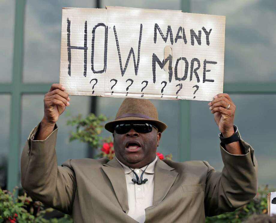 Rev. Dr. Arthur Prioleau holds a sign during a protest in the shooting death of Walter Scott at city hall in North Charleston, S.C., Wednesday, April 8, 2015.  Scott was killed by a North Charleston police office after a traffic stop on Saturday. The officer, Michael Thomas Slager,  has been charged with murder. (AP Photo/Chuck Burton) Photo: Chuck Burton, STF / AP