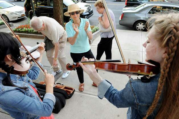 Betsy Tick of Saratoga Springs, center, claps along to the music of buskers, Seina Shirakura, 18, left, and Ali Genevich, 16, both classically-trained violinists who play fiddle tunes for tips, on Broadway on Thursday, July 10, 2014, in Saratoga Springs, N.Y. (Cindy Schultz / Times Union archive) Photo: Cindy Schultz / 00027672A