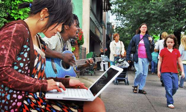 Suxin Cheah, left, works on her laptop as George Samuels, both of Saratoga Springs, plays guitar and sings on a sidewalk bench along Broadway in Saratoga Springs Monday afternoon August 11, 2008. (John Carl D'Annibale/Times Union archive) Photo: John Carl D'Annibale / Albany Times Union