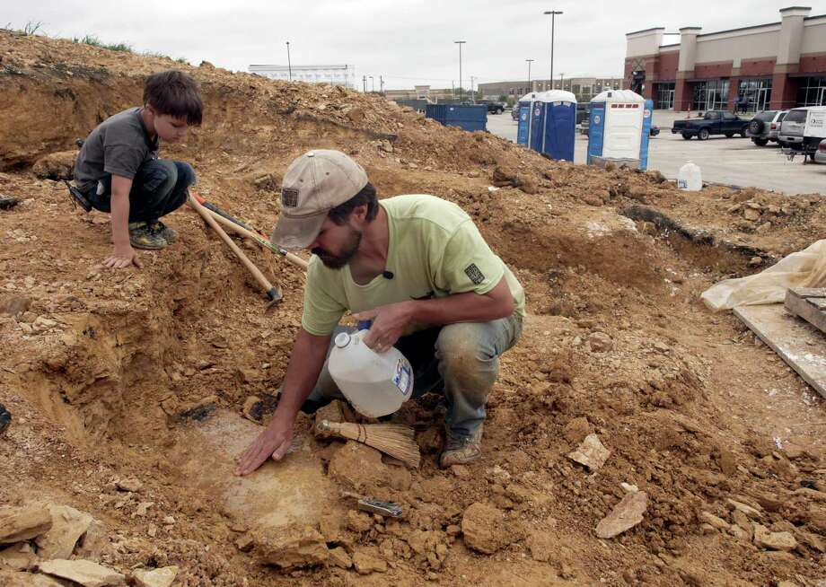 Wylie Brys, 5, and his dad, Tim Brys continue to look for fossils in the same spot where Wylie found the fossilized bones of a nodosaur last September, in Mansfield, Texas, Tuesday April 7, 2015. Brys, who works at the Dallas Zoo, found the 100 million-year-old fossil with his son Wylie on a patch of land behind a grocery store at Matlock Road and Debbie Lane. On Tuesday, Southern Methodist University scientists helped Brys and son excavate the fossil.  (AP Photo/The Dallas Morning NewsRon Baselice) Photo: Ron Baselice, MBR / The Dallas Morning News