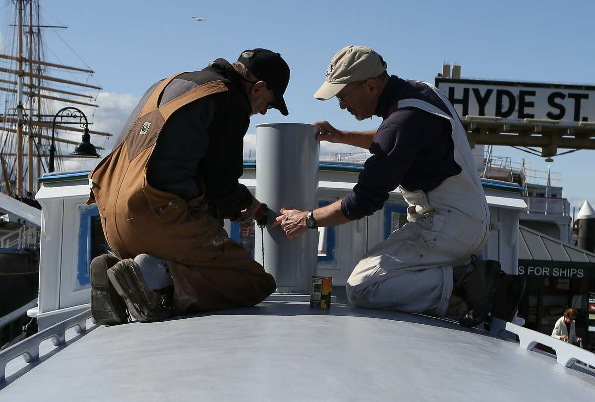 Volunteers Rod Baker (left) and George Ushanoff work on completing the final touches on the rebuilt Eva B at the Maritime National Historical Park in San Francisco, Calif., on Wednesday, April 8, 2015.