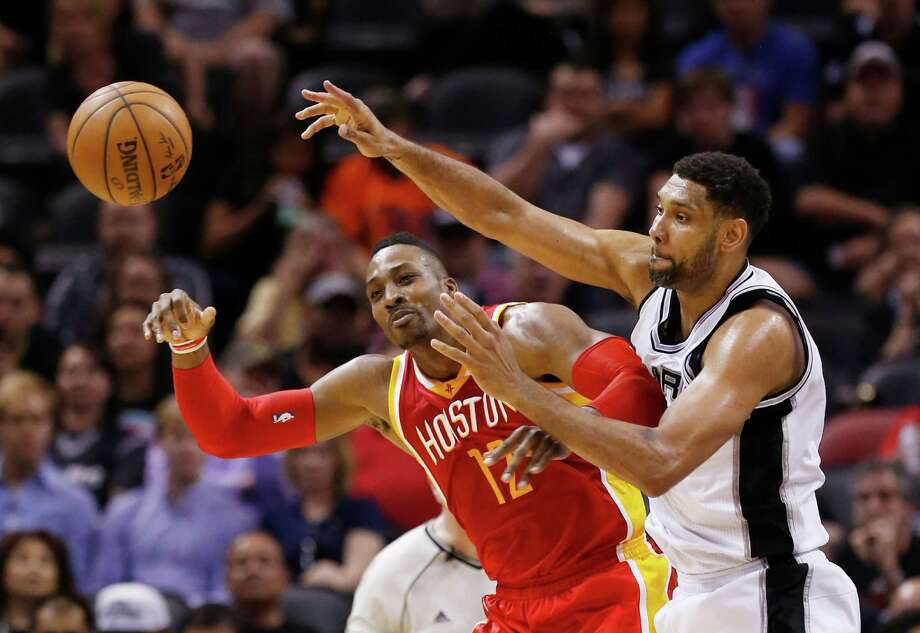 The Spurs' Tim Duncan, right, fouls Dwight Howard during a first-half scramble. Photo: Kin Man Hui, Staff / ©2015 San Antonio Express-News