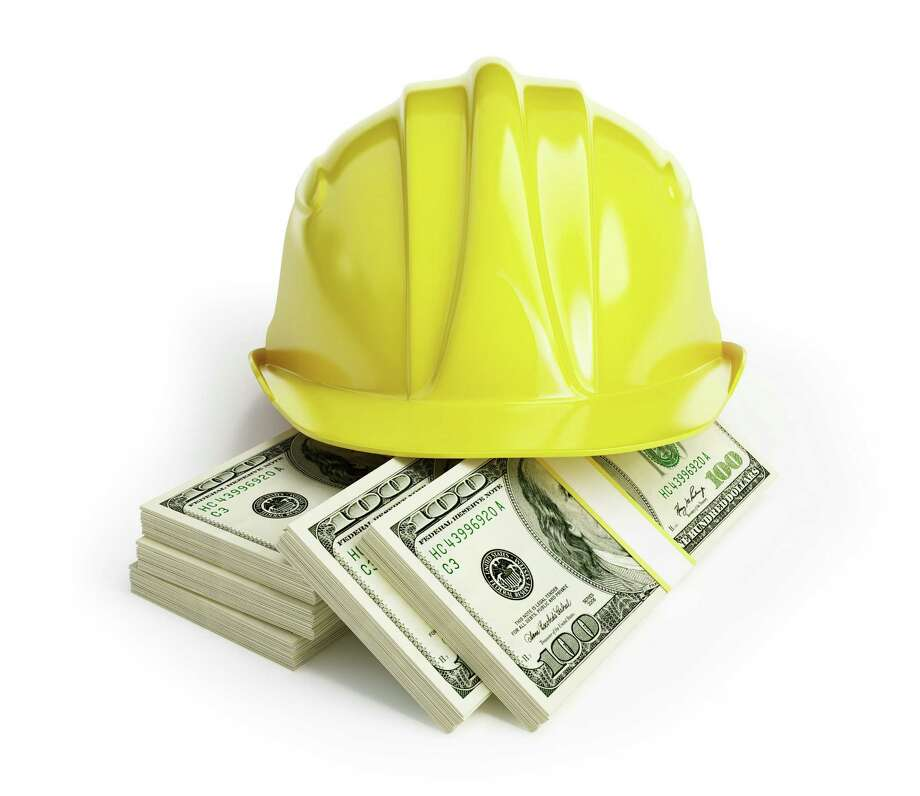 Workers' wages, hard hat, money workers' wages on a white background Photo: Fotolia / 3desc - Fotolia
