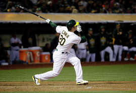 A's first baseman Mark Canha drives in a run with a double against the Rangers during the sixth inning. Canha, who played at Cal, had three hits, with two doubles and four RBIs, in his major-league debut.
