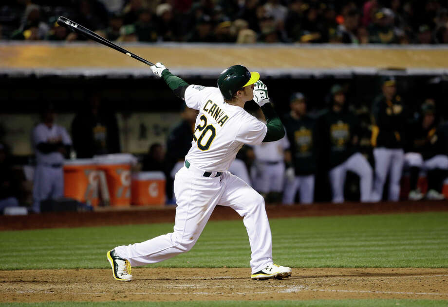 A's first baseman Mark Canha drives in a run with a double against the Rangers during the sixth inning. Canha, who played at Cal, had three hits, with two doubles and four RBIs, in his major-league debut. Photo: Marcio Jose Sanchez / Associated Press / AP