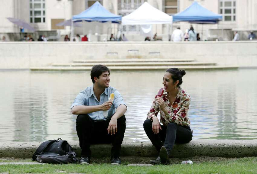 Behram Rair and Ayesha Akhtar enjoy frozen treats at the weekly farmer's market in Hermann Square Wednesday, April 8, 2015, in Houston.