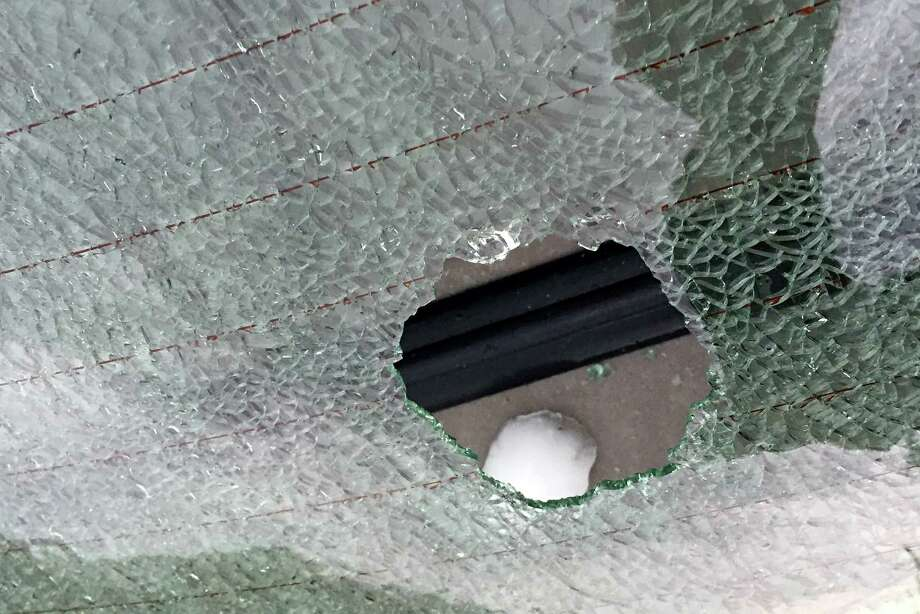 A hail stone slightly smaller than a tennis ball sits on the rear deck of a car after it smashed the rear window of the car in downtown Farmington on Wednesday, April 8, 2015. Numerous cars sustained broken windows from the hail.  EDWARDSVILLE INTELLIGENCER OUT, THE ALTON TELEGRAPH OUT Photo: David Carson, AP / St. Louis Post-Dispatch