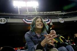 Eireann Dolan, girlfriend of Athletics relief pitcher Sean Doolittle, watches Wednesday's game between the A's and Rangers. Dolan raised nearly $35,000 to bring LGBT youth to the park for the team's pride night on June 17.