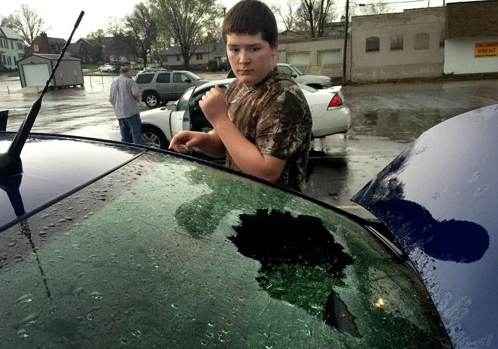 Derek Smith, 14, from Bonne Terre, looks at the shattered rear window of his mom's car that was busted out by hail slightly smaller than a tennis ball that fell from a storm in downtown Farmington, Mo., Wednesday, April 8, 2015. Numerous cars sustained broken windows from the hail. EDWARDSVILLE INTELLIGENCER OUT, THE ALTON TELEGRAPH OUT