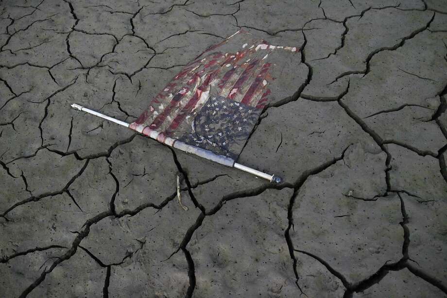 An American flag lays perfectly flat on the freshly exposed bottom of Lake McClure as it sits at about 8 percent capacity Sept 28, 2014, in Snelling (Merced County). Photo: Leah Millis