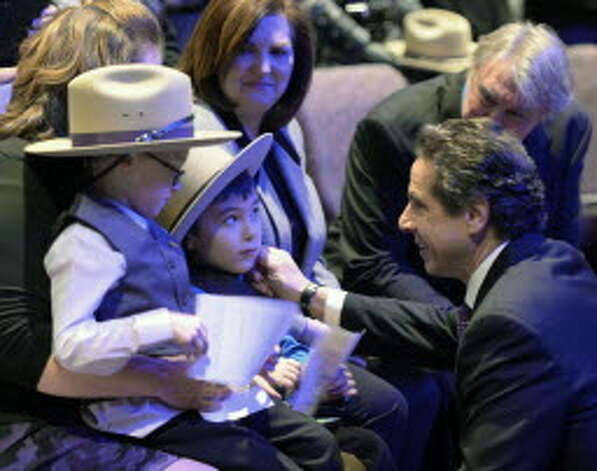 Gov. Andrew Cuomo speaks to Zachery and Caleb Cunniff at the funeral service of their father, Trooper David Cunniff Friday, Dec. 20, 2013, at Grace Fellowship Church in Colonie, N.Y. (AP Photo/The Albany Times Union, Skip Dickstein, Pool)