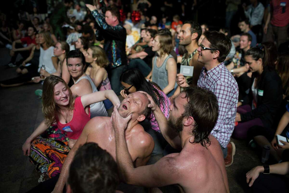 Mac Murphy, right, and Marnie Brumder, left, massage Eric Monkhouse's head after dancing at Daybreaker, a device-free dance party hosted by Digital Detox and Camp Grounded, at Inner Mission in San Francisco, Calif. on Thursday, April 9, 2015.