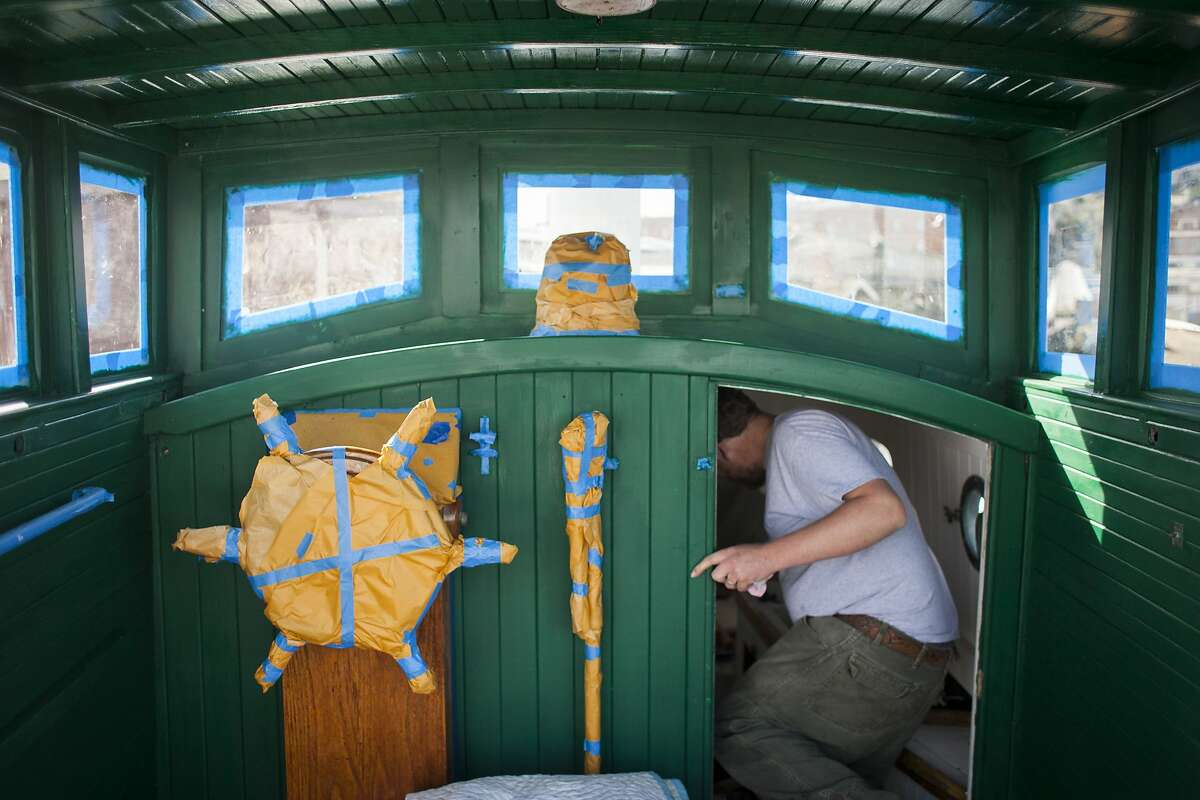 Karnell Hillscan, a museum specialist with the national park service, steps into the restored cabin of the Eva B., a 30 foot long wooden boat brought back to life after 5 years of restoration at the Hyde Street Pier in San Francisco on April 9th 2015.