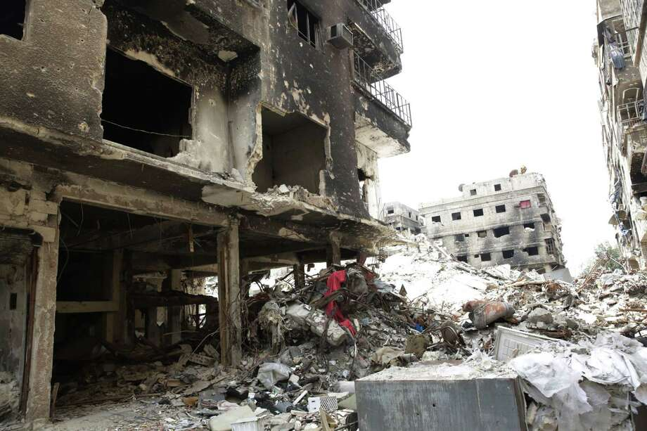 Rubble and heavy damage remain on a deserted street during a government escorted visit to Yarmouk refugee camp in Damascus. Photo: Associated Press / AP