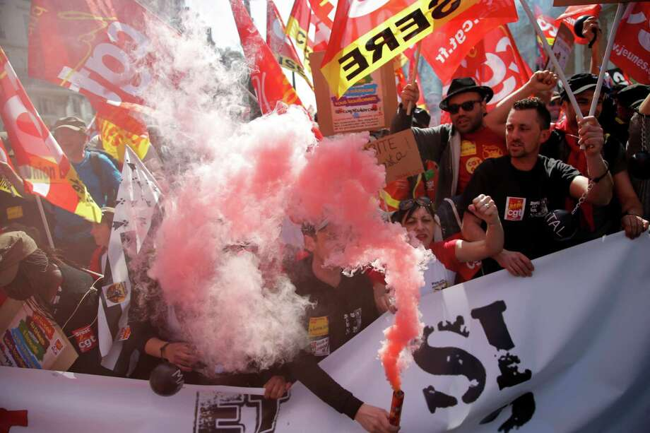 Demonstrators holding flares and union flags chant slogans as part of a demonstration march in Paris, 15 during a nationwide day of protests and strikes over an array of grievances against the government. Photo: Francois Mori / Associated Press / AP