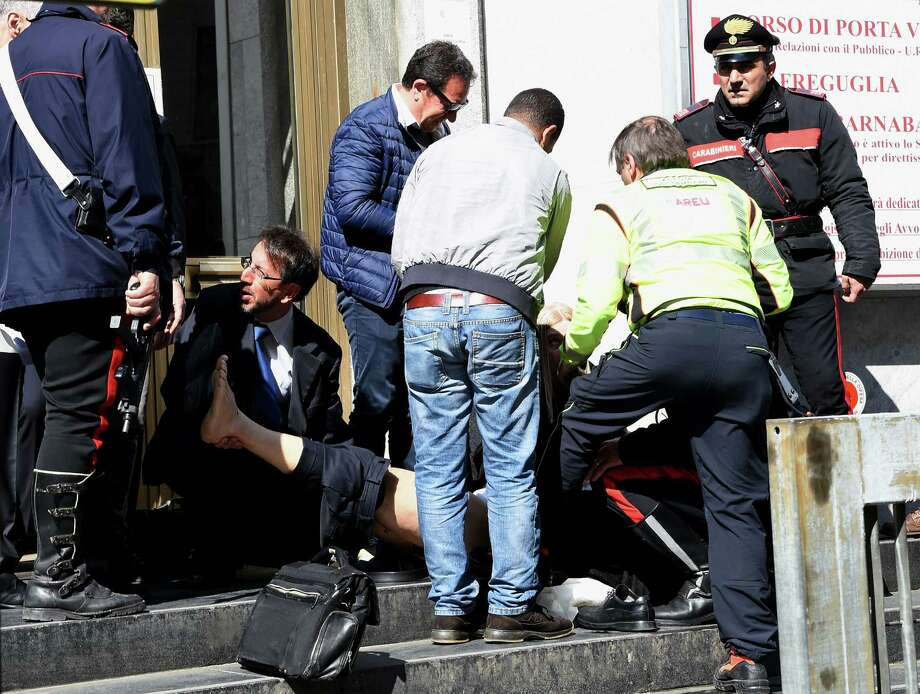 People help an injured man outside a Milan courthouse after an armed man facing bankruptcy shot three people dead and wounded two others. Photo: OLIVIER MORIN / AFP / Getty Images / AFP