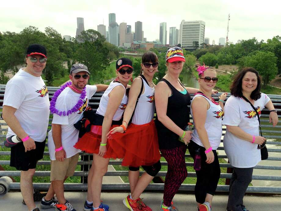 Hot Tatamales teammates, from left, Dan Evans, Eric Christian Smith, Donna Evans, Meredith Raine, Kristy Charroin, Betsy Zumwalt and Kimberly Tabor stop for a photo of downtown Houston near Buffalo Bayou during last year's Avon walk. Photo: Jill Karnicki / Houston Chronicle