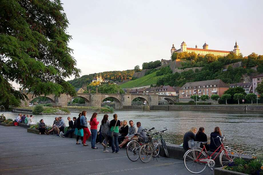 Bring a picnic to the riverbank in Würzburg, Germany, to enjoy a fortress view and convivial people.  RS14Summer_044.jpg Photo: Rick Steves