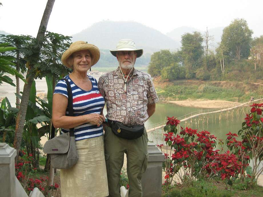 Carol and Kenneth Laidlaw of Oakland  Cheerful tourists with Mekong tributary in background - note smokey sky from slash and burn farming