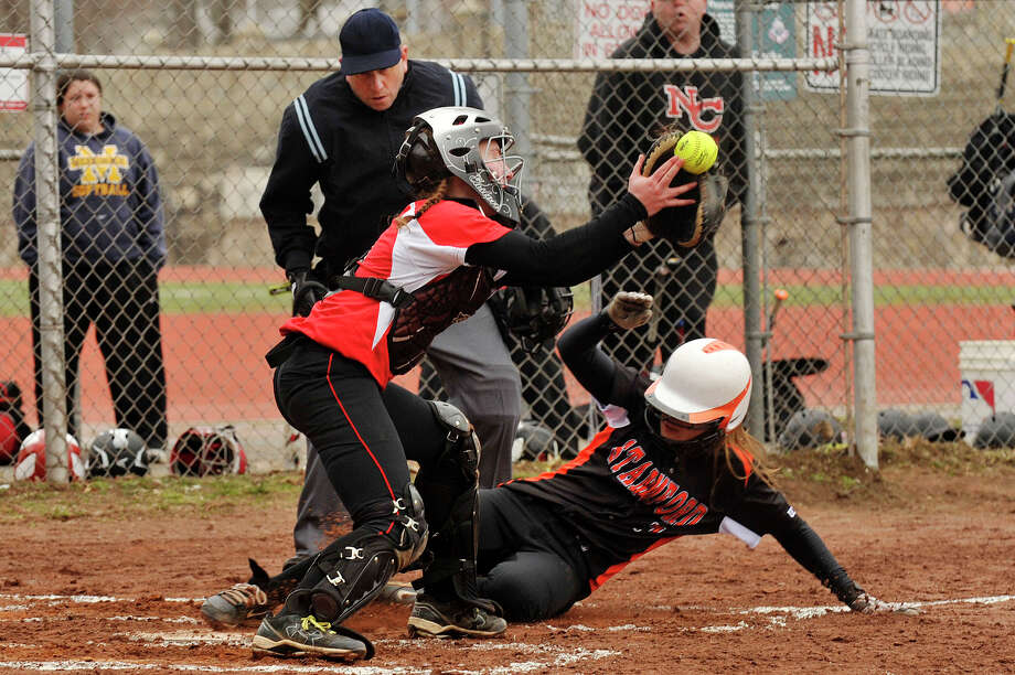 Stamford's Kelly DiPietro slides safely into home with a late throw to New Canaan catcher Molly Keshin during their softball game at Stamford High School in Stamford, Conn., on Thursday, April 9, 2015. Stamford won, 12-2 after five innings. Photo: Jason Rearick / Stamford Advocate
