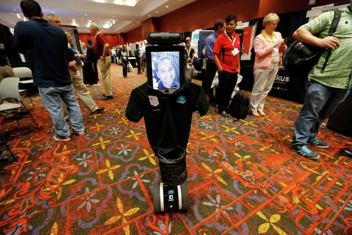 Manuel Oblitas of Visual Net Design of San Antonio is seen on a video display of a Double telepresence robot Thursday while roaming the exhibition hall at the 2015 InnoTech San Antonio conference at the Convention Center.