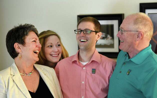 Kim McFarlane, left, gave a kidney to Tom Adams, second from right, is joined by Tom's wife Hillary Adams, second from left, and Blair McFarlane, Kim's husband, right, Wednesday morning April 8, 2015, at Tom's home in Saratoga Springs, N.Y.  He received a kidney from Kidney Kim McFarlane in February. (Skip Dickstein/Times Union) Photo: SKIP DICKSTEIN / 00031265A