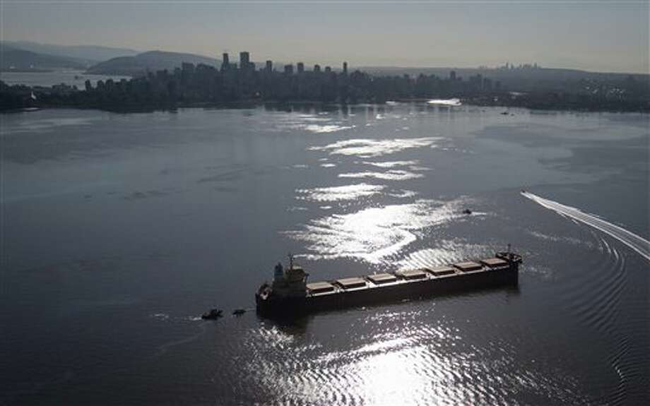 Spill response boats work to contain fuel leaking from the bulk carrier cargo ship Marathassa, anchored on Burrard Inlet, Thursday, April 9, 2015, in Vancouver, British Columbia. The slow response to the bunker oil spill galvanized worry about a pipeline terminus and oil tanker terminal proposed for nearby Burnaby. The pipeline was approved Thursday by the National Energy Board of Canada. (AP Photo/The Canadian Press, Darryl Dyck) Photo: DARRYL DYCK, AP / The Canadian Press