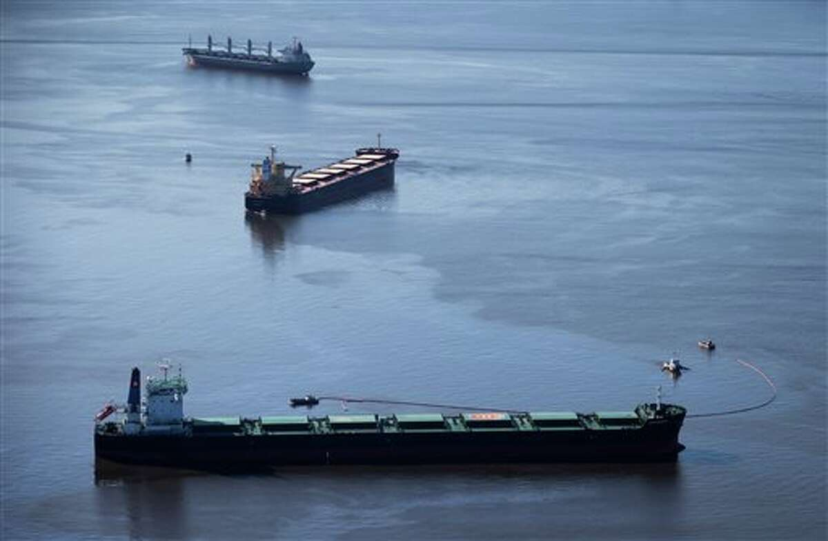 A small spill that had big consequences: Spill response boats work to contain fuel leaking from the bulk carrier cargo ship Marathassa, middle, anchored on Burrard Inlet, Thursday, April 9, 2015, in Vancouver, British Columbia. The City of Vancouver warned that the fuel is toxic and should not be touched. (AP Photo/The Canadian Press, Darryl Dyck)
