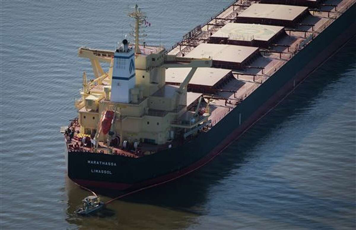 A spill response boat monitors a boom placed around the bulk carrier cargo ship Marathassa, Thursday, April 9, 2015, in Vancouver, British Columbia. If a proposed 895,000 barrels a day oil pipeline from Alberta is built, 34 laden oil tankers would traverse Vancouver's Burrard Inlet and English Bay each month.