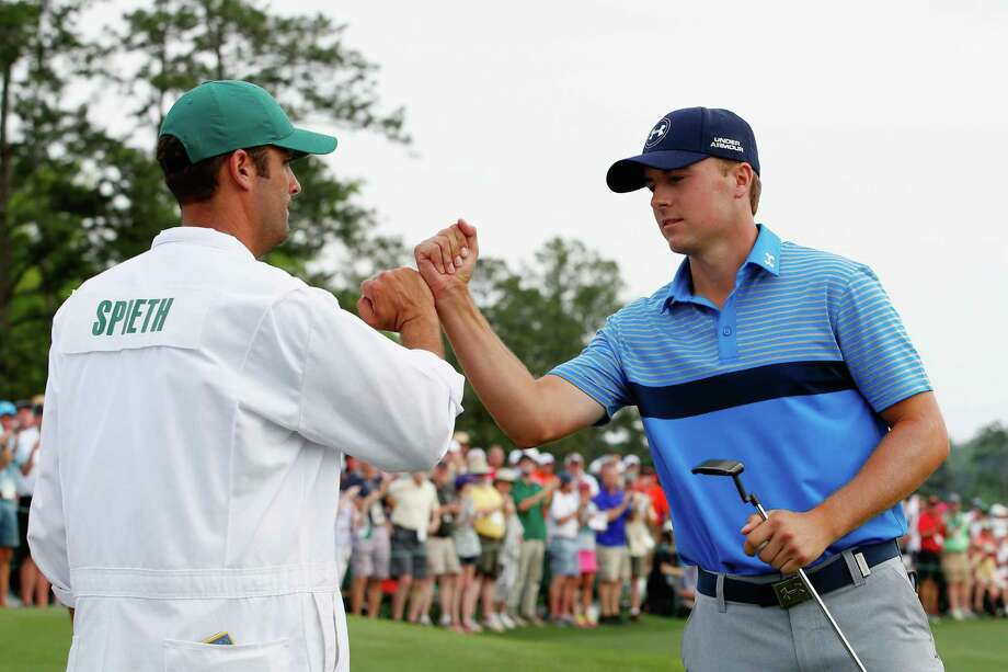 AUGUSTA, GA - APRIL 09:  Jordan Spieth of the United States celebrates with his caddie Michael Greller on the 18th green after an eighth-under par 64 during the first round of the 2015 Masters Tournament at Augusta National Golf Club on April 9, 2015 in Augusta, Georgia.  (Photo by Ezra Shaw/Getty Images) Photo: Ezra Shaw, Staff / Getty Images / 2015 Getty Images