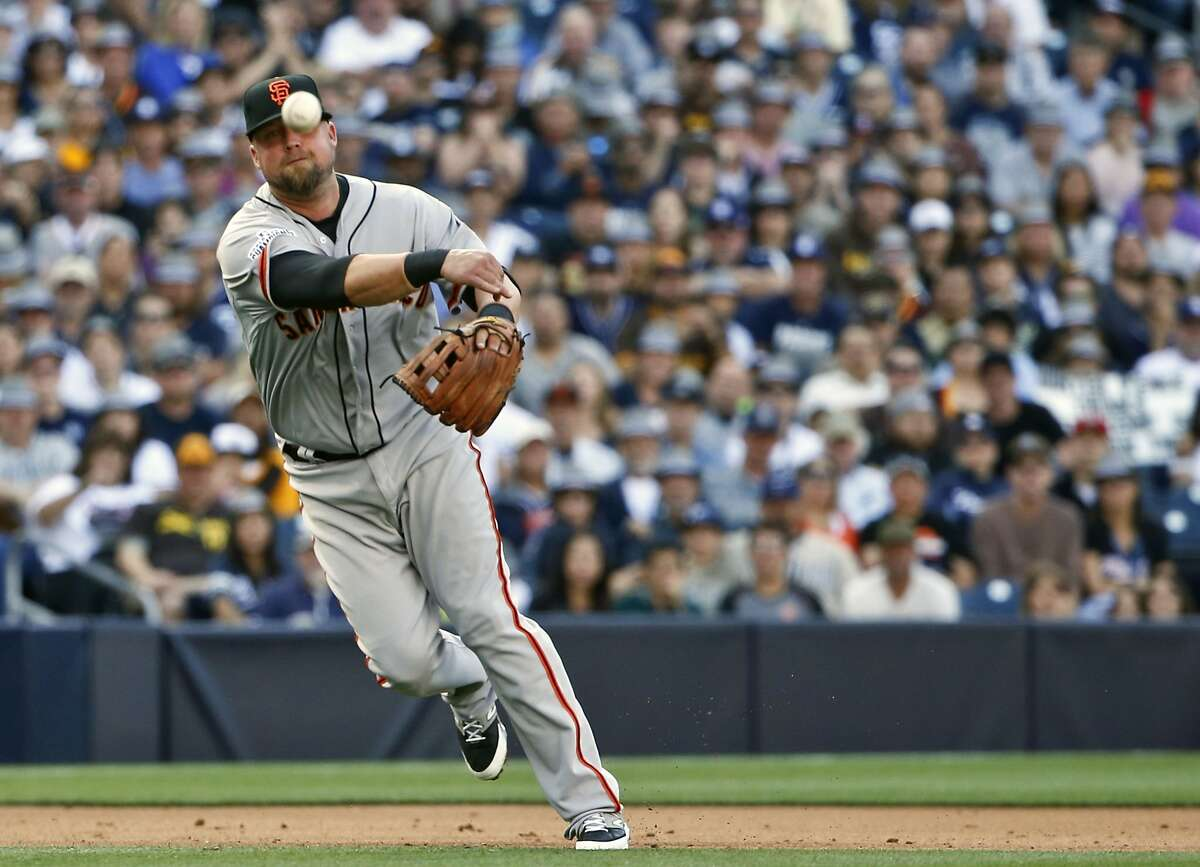 San Francisco Giants third baseman Casey McGehee makes a hurried throw to first to get San Diego Padres' Matt Kemp after first booting the ground ball in the fourth inning of a baseball game Thursday, April 9, 2015, in San Diego. (AP Photo/Lenny Ignelzi)